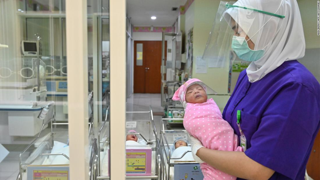 A nurse holds a newborn baby, wearing a face shield as a protective measure, at a maternity facility in Jakarta, Indonesia.