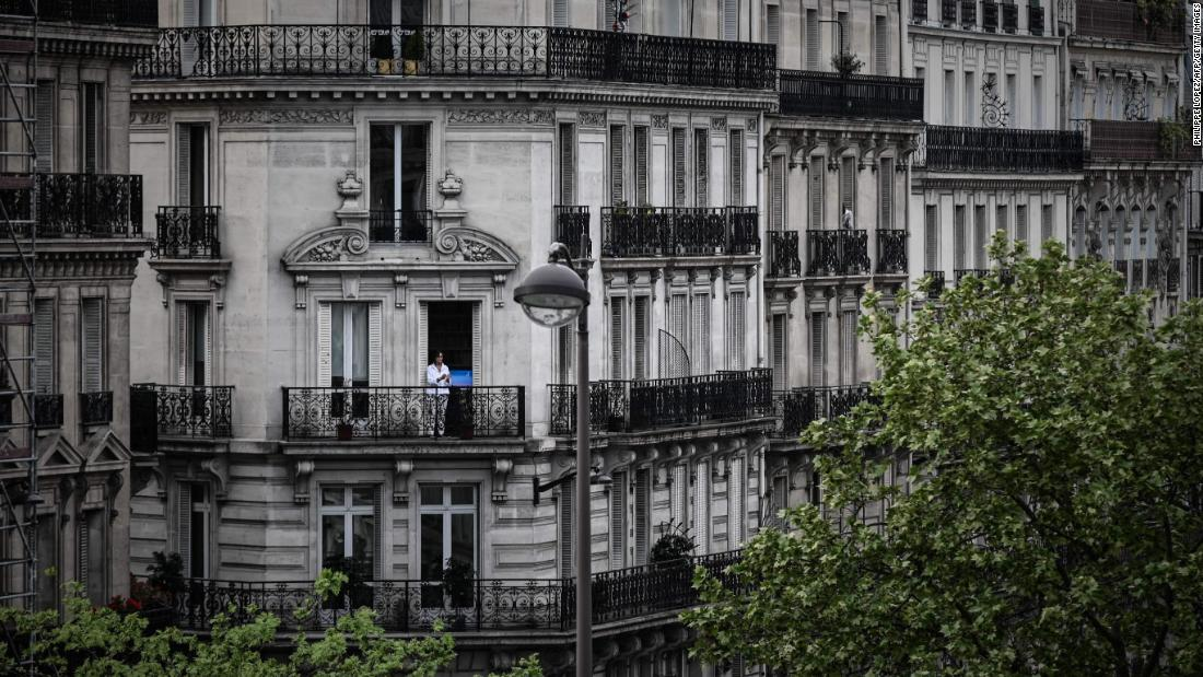 A woman applauds from the balcony of her Paris home to show support for health care workers on April 20, 2020.