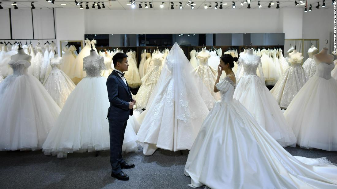 A couple try on a suit and a wedding dress at a wedding service company in Shijiazhuang, Hebei province, China, on April 8.