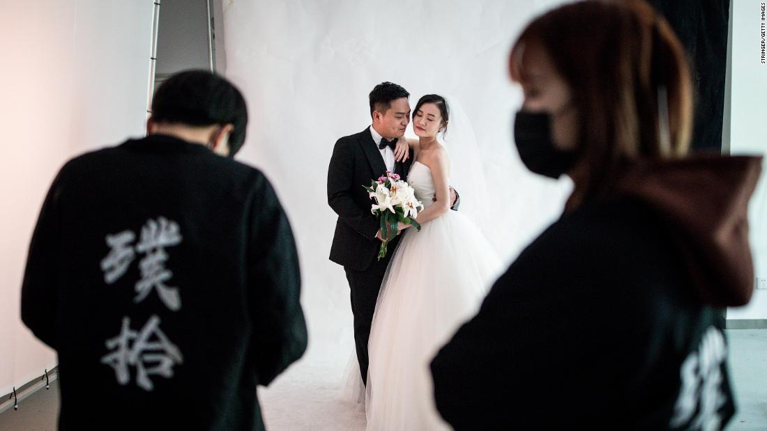 A couple pose for photos at the Pushi wedding photography studio in Wuhan, Hubei province, China, on April 15. People in Wuhan have restarted wedding preparations as the coronavirus outbreak there appears to be waning.