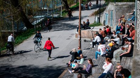 People enjoy the warm spring weather as they sit by the water at Hornstull in Stockholm on April 21 during the COVID-19 pandemic.