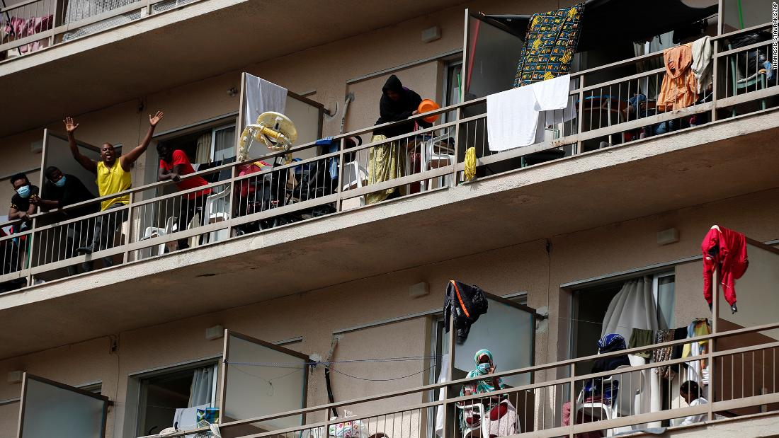 Migrants wave from balconies at a hotel in Kranidi, Greece, on April 21, 2020. The shelter, which hosts 470 asylum seekers, was placed in isolation after a pregnant resident tested positive for the novel coronavirus.