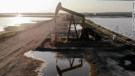 Global oil prices hit 21-year low but stock markets edge higher