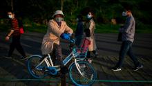 A woman wearing a face mask takes a rest on a bicycle along the East Lake in Wuhan after its lockdown was lifted.