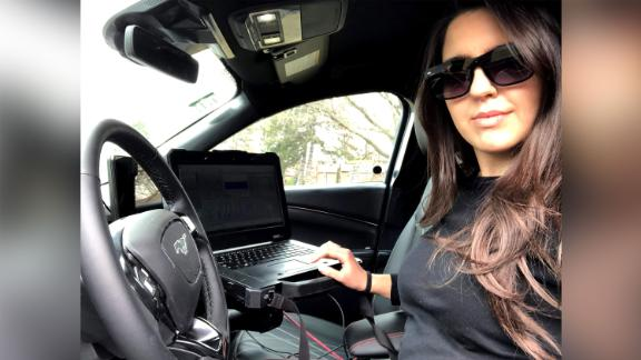 Ford engineer Aleyna Kapur in the driver's seat of a Ford Mustang Mach-E test vehicle with a laptop to record data.