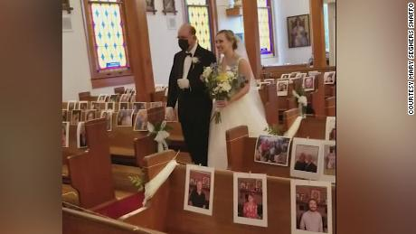Clare Keefer is walked down the aisle by her father in the church, decorated with pictures of their guests.