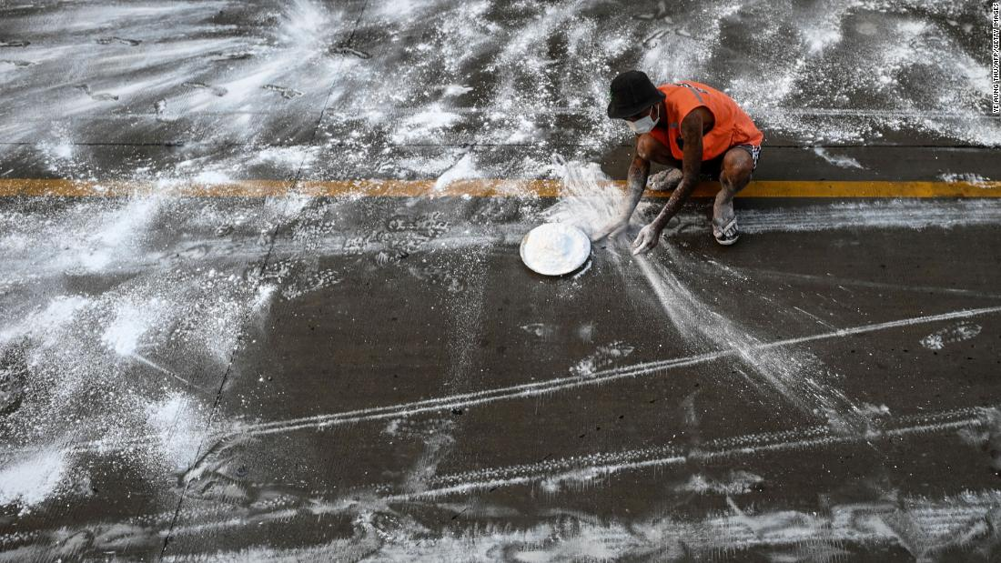 A volunteer in Yangon, Myanmar, spreads calcium oxide on a road to help prevent the spread of the coronavirus on April 22, 2020.