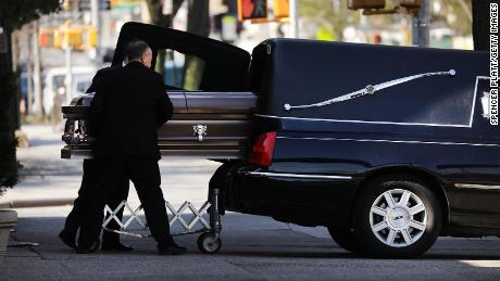 A casket is placed into a hearse outside of a funeral home in Brooklyn.