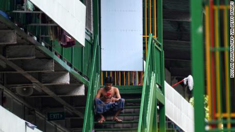 A migrant worker rests on a staircase at a dormitory in Singapore, on April 22.