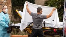 Healthcare workers transport a patient on a stretcher into an ambulance at Life Care Center of Kirkland in Washington state. (David Ryder/Getty Images)