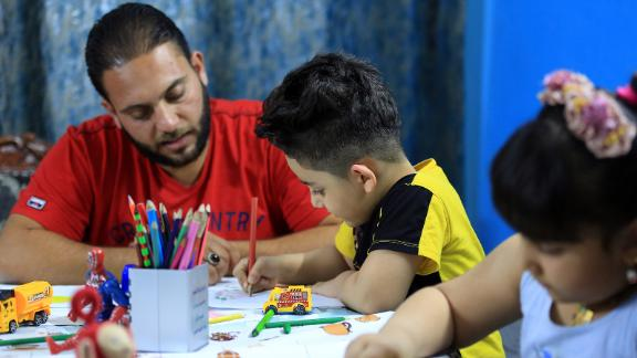 An Iraqi father, Mustafa C., is seen with his children, Rukayye and Ali, who are painting to draw attention to the novel coronavirus during a day of quarantine in Baghdad, Iraq, on April 18, 2020.