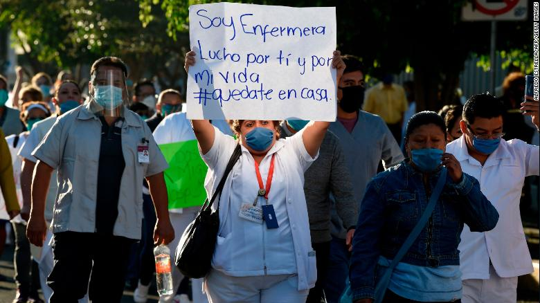 """A health worker hold a sign reading, """"I am a nurse. I fight for you and for my life,"""" as she takes part in a protest in demand of medical material to care for COVID-19 patients, in Mexico City on April 13."""