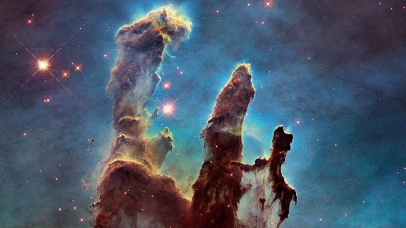 """Astronomers combined several Hubble images taken in 2014 to create an upgraded view of the Hubble's iconic 1995 """"Pillars of Creation"""" image. The new image shows a wider view of the pillars, which stretch about 5 light-years high. The pillars are part of a small region of the Eagle Nebula, which is about 6,500 light years from Earth."""