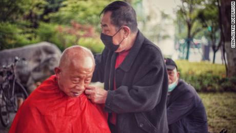 A man gets his haircut at an outdoor barber in a Wuhan park on April 23.