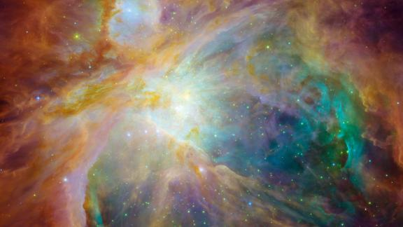 Hubble also teamed up with Spitzer to create this stunning image of the Orion Nebula in 2006. The image combines visible, infrared and ultraviolet light. A community of massive stars is represented by the yellow at the heart of the image.