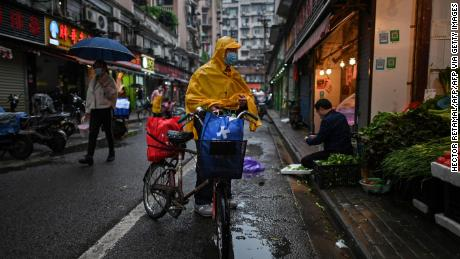 A man wearing a face mask arrives to buy vegetables at a stall in Wuhan in China's central Hubei province on April 18.