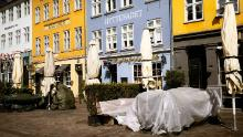 Tables are covered up outside shuttered restaurants in the popular tourist area of Nyhavn in Copenhagen, Denmark, on April 15.