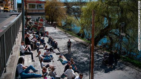 People enjoy the warm spring weather as they sit by the water at Hornstull in Stockholm on April 21.