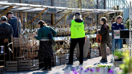 "An employee wears a vest reading ""Keep distance. Stop Covid-19"" as customers look at plants at the Slottstradgarden Ulriksdal garden centre in the Ulriksdal Palace park in Stockholm on April 21."