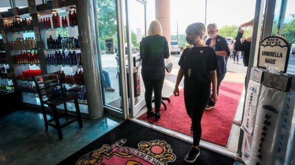 Employees and customers walk in to Three-13 Salon, Spa & Boutique on Friday, April 24, 2020, in Marietta, Ga. The salon had been closed for more than a month due to the new coronavirus. Barber shops, nail salons, gyms and a few other businesses reopened in Georgia on Friday as the Republican governor eased a month-long shutdown despite warnings from health experts of a potential new surge of coronavirus infections