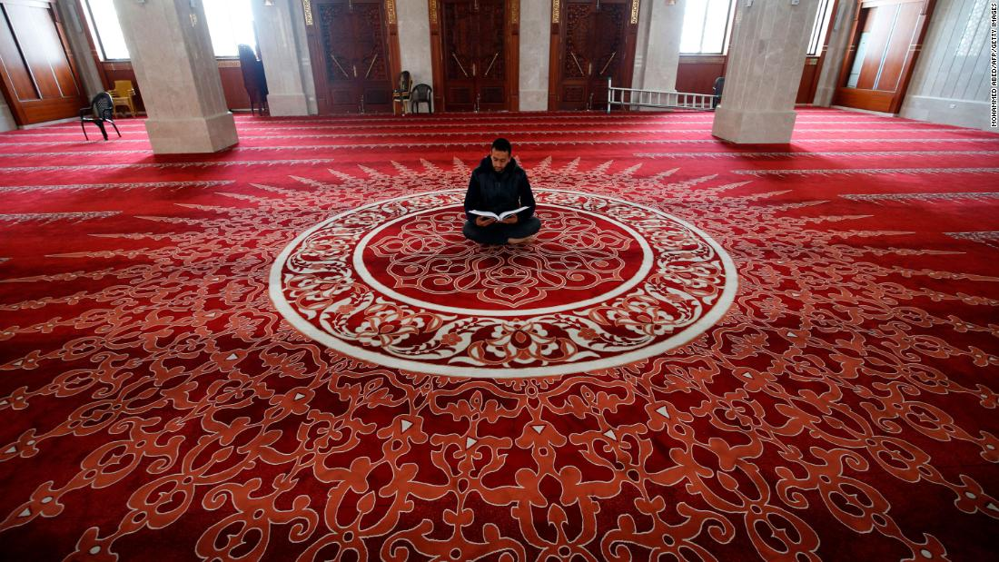 "A muezzin, the person at a mosque who calls Muslims to daily prayers, reads the Quran at a mosque in Gaza City after <a href=""http://www.cnn.com/2020/04/23/world/gallery/ramadan-2020/index.html"" target=""_blank"">Ramadan began</a> on April 24, 2020."
