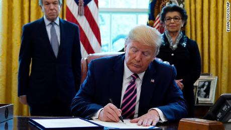 President Donald Trump signs a coronavirus aid package to direct funds to small businesses, hospitals, and testing, in the Oval Office of the White House, Friday, April 24, 2020, in Washington. Sen. Roy Blunt, R-Mo., left, and Jovita Carranza, administrator of the Small Business Administration look on.