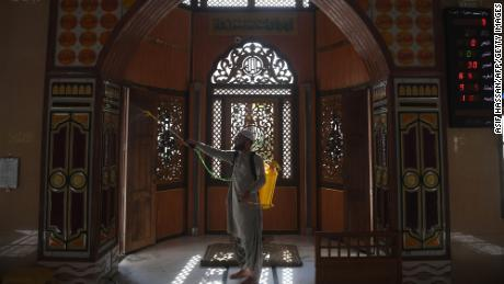 A Muslim devotee sprays disinfectant in a mosque ahead of the Muslim holy month of Ramadan during a government-imposed nationwide lockdown in Karachi on April 23, 2020.