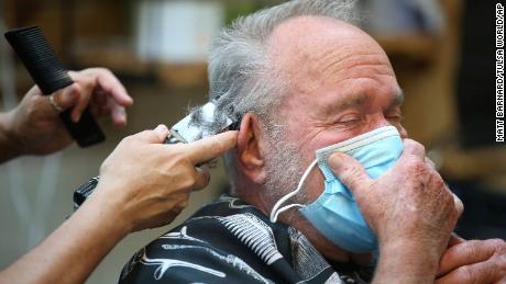 Lonnie Sullivan couvre son visage avec un masque tout en se faisant couper les cheveux au salon de coiffure de Broken Arrow, Oklahoma, le vendredi 24 avril.