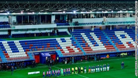 Eibar SAD and Real Sociedad players lined up in an empty stadium on March 10 after fans were barred from attending the match due to the coronavirus pandemic.