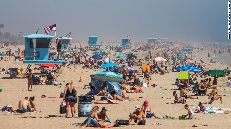 People enjoy the beach amid the novel coronavirus pandemic in Huntington Beach, California on April 25, 2020.
