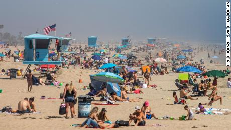 People enjoy the beach amid the novel coronavirus pandemic in Huntington Beach, California, on April 25, 2020.