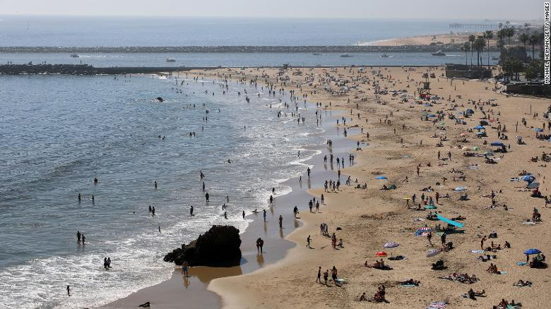 People are seen gathering on the Corona del Mar State Beach on April 25, 2020 in Newport Beach, California.