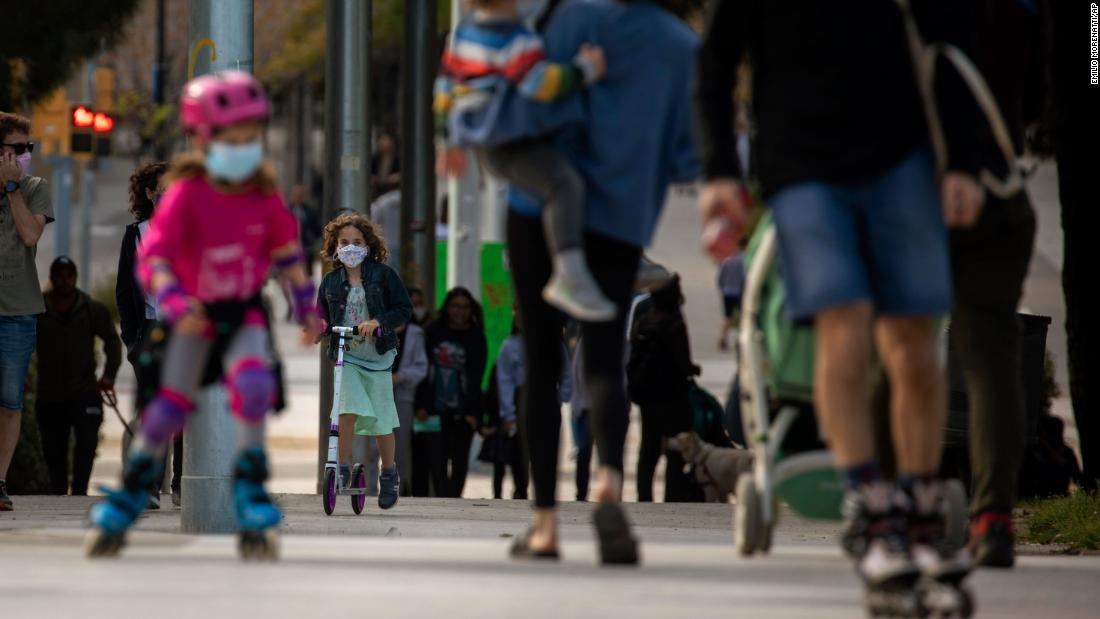 "Families walk along a boulevard in Barcelona, Spain, on April 26. The government now allows children<a href=""https://www.cnn.com/world/live-news/coronavirus-pandemic-04-26-20-intl/h_7d4e57bbfadc52a651f777cc7cff219c"" target=""_blank""> to go out once a day,</a> for one hour, within about half a mile of their homes, with one adult who lives with them. Up to three kids can go with each adult."