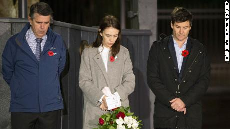 New Zealand Prime Minister Jacinda Ardern stands at dawn on the driveway of Premier House with her father Ross Ardern, left, and partner Clarke Gayford to commemorate Anzac Day in Wellington, New Zealand, on April 25, 2020.