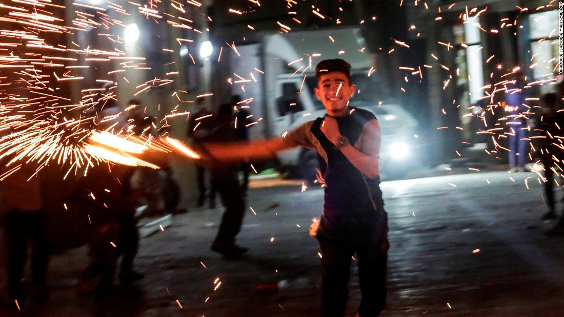A Palestinian youth swings a homemade sparkler while celebrating the Holy month of Ramadan on April 26, in the northern Gaza Strip. In Jabalia camp in the northern Gaza Strip From cancelled iftar (fast breaking) feasts to suspended mosque prayers, Muslims across the Middle East are bracing for a bleak month of Ramadan fasting as the threat of the COVID-19 pandemic lingers. The holy Muslims fasting month of Ramadan is a period for both self-reflection and socialising. Believers fast from dawn to dusk and then gather around a family or community for a meal each evening of Islam's holiest month. (Photo by Mahmoud Issa / SOPA Images/Sipa USA)(Sipa via AP Images)