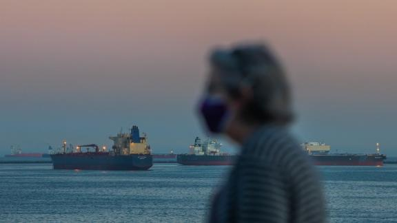 A woman wearing face mask walks on the ocean front while Oil tankers are seen anchored off the coast of Long Beach, California, after sunset on April 25, 2020. - According to a news release issued by the United States Coast Guard, there were 27 tankers off the Southern California coast as of April 23 afternoon. Companies are using the tankers to store excess supplies of crude oil due to lack of demand during the novel coronavirus pandemic, US media reported. (Photo by Apu Gomes/AFP/Getty Images)