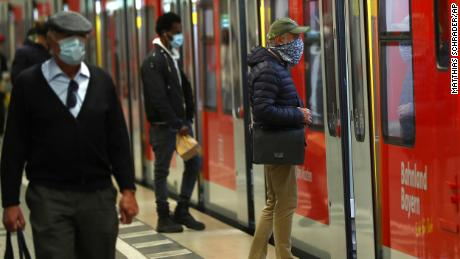 People wear masks at the central station in Munich, Germany, on Monday.