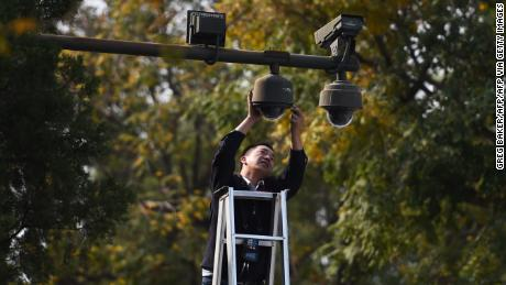 A worker adjusts security cameras on the edge of Tiananmen Square in Beijing on September 30, 2014.
