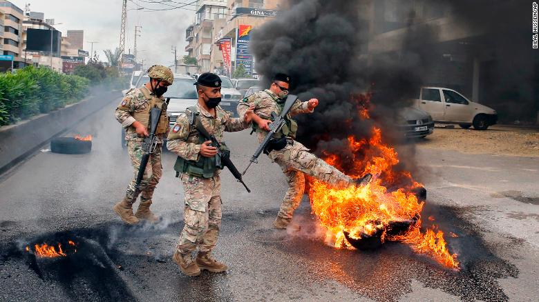 Lebanese soldiers remove burning tires placed by anti-government protesters to block a road.