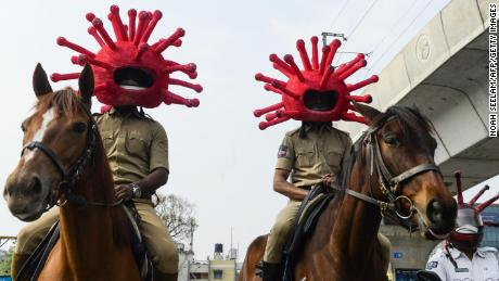 Police personnel wearing coronavirus-themed helmets ride on horses as they participate in a awareness campaign in Secunderabad, the twin city of Hyderabad, on April 2, 2020.