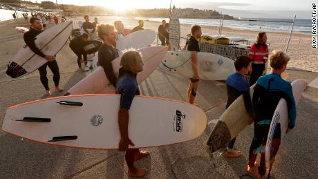 Surfers wait for officials to open Bondi Beach in Sydney on April 28 as coronavirus pandemic restrictions are eased. The beach is open to swimmers and surfers to exercise only.
