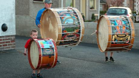 "Mark Black and his sons, Thomas, left, four, and Adam, 10, play Lambeg drums outside their home during the weekly ""Clap for our Carers"" in County Armagh, Northern Ireland, Thursday, April 16, 2020. The applause takes place across Britain and Northern Ireland every Thursday at 8pm local time to show appreciation for healthcare workers, emergency services, armed services, delivery drivers, shop workers, teachers, waste collectors, manufacturers, postal workers, cleaners, vets, engineers and all those helping people with coronavirus and keeping the country functioning while most people stay at home in the lockdown. (Niall Carson/PA via AP)"