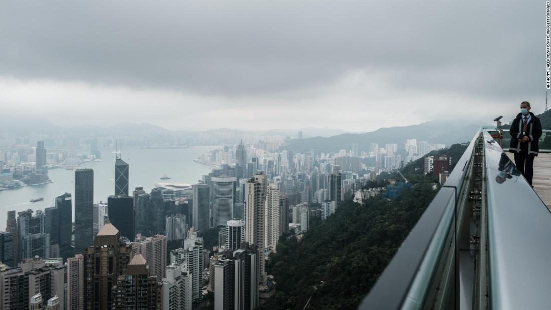A security guard wears a face mask, as a precautionary measure against the COVID-19 coronavirus, as he stands on an empty viewing deck at the usually busy tourist attraction, Victoria Peak, in Hong Kong on April 7, 2020. (Photo by Anthony WALLACE / AFP) (Photo by ANTHONY WALLACE/AFP via Getty Images)