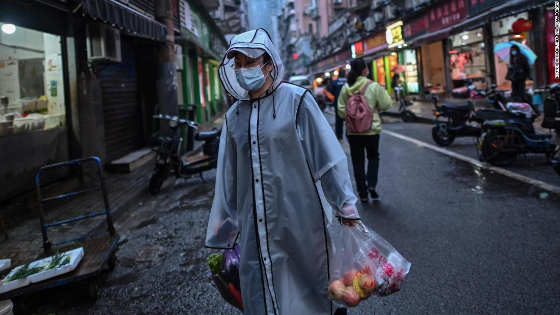 A person wearing a face mask as a preventive measure against the spread of the COVID-19 novel coronavirus carries groceries in a neighbourhood in Wuhan in China's central Hubei province on April 20, 2020. - A bride in a white gown poses by Wuhan's East Lake while a grandfather swings his tiny grandson in a hammock strung between trees, and families enjoy a picnic on a sunny afternoon: Wuhan is returning to normal after enduring a 76-day quarantine. (Photo by Hector RETAMAL / AFP) / TO GO WITH Health-virus-China-Wuhan,FOCUS by Jing Xuan Teng (Photo by HECTOR RETAMAL/AFP via Getty Images)