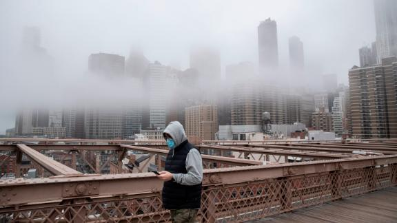 NEW YORK, NY - MARCH 20: A man wearing a mask walks the Brooklyn Bridge in the midst of the coronavirus (COVID-19) outbreak  on March 20, 2020 in New York City. The economic situation in the city continued to decline as New York Gov Andrew Cuomo ordered all nonessential businesses to keep all their workers at home and New York weighed a shelter in place order for the entire city. (Photo by Victor J. Blue/Getty Images)