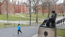 A runner crosses an empty Harvard Yard last month, after students were asked to finish the semester online.