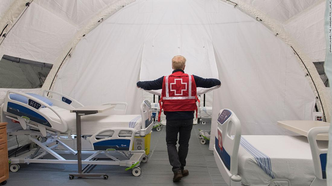 Red Cross volunteer Stephane Corbeil adjusts an opening in a tent at a mobile hospital at Jacques Lemaire Arena in the Montreal suburb of LaSalle, Sunday, April 26, 2020, during the COVID-19 pandemic. (Graham Hughes/The Canadian Press via AP)