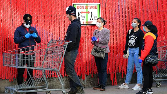 Customers wait in line in front of a sign recommending social distancing to enter the Industry City Costco store on April 28, in the Brooklyn borough of New York City.