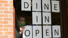 A man hangs up signs to to promote dine-in service available at a restaurant in Brookhaven, Georgia, on April 27.