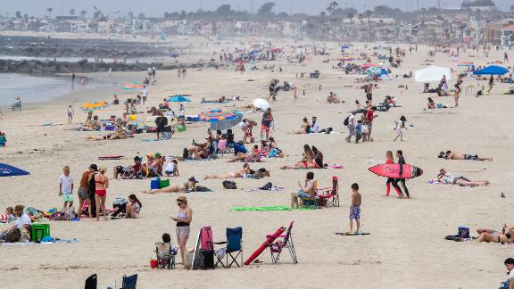 NEWPORT BEACH, CA -- TUESDAY, APRIL 28, 2020:  Beach-goers enjoy a partially-sunny, warm day on the beach near the pier in Newport Beach, CA, on April 28, 2020.  Newport Beach City Council members are holding a special meeting to discuss closing the city's beaches for the next few weekends following Gov. Gavin Newsom's criticism of the large crowds and lack of social distancing.(Allen J. Schaben / Los Angeles Times via Getty Images)